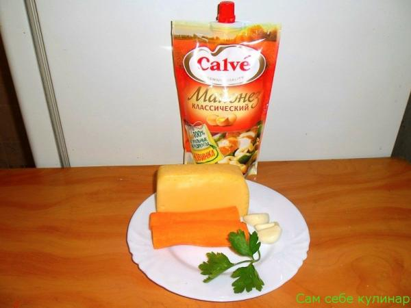 кусок сыра морковь чеснок на тарелке пачка майонеза кальве