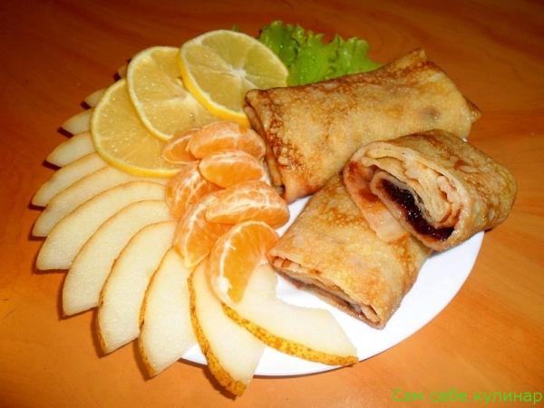 Блинчики сладкие с вареньем на тарелке с фруктами