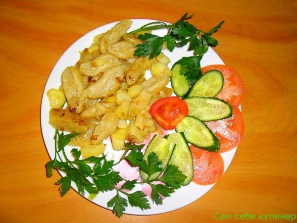 Галушки украинские на тарелке с овощами и зеленью