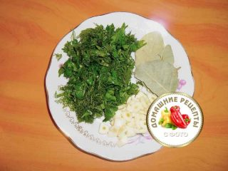 нарезанная зелень, порубленный чеснок и лавровый лист на тарелке
