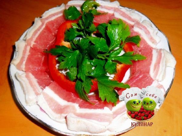грудинка нарезанная на тарелке с зеленью