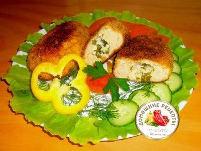 Котлеты по киевски из фарша на тарелке с листьями салата