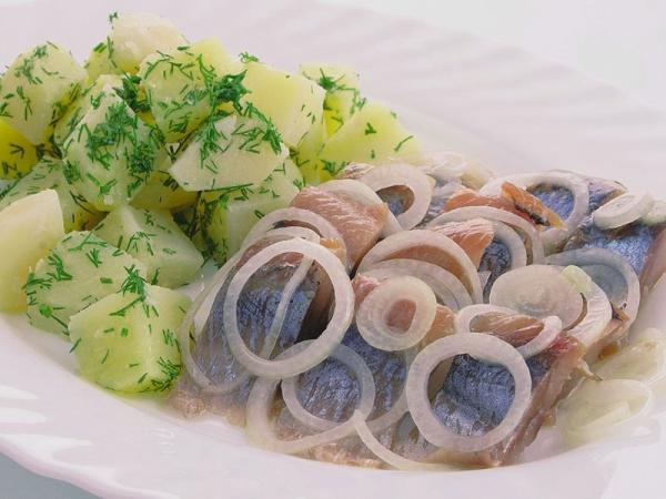 сельдь кусочками на блюде картошка с укропом
