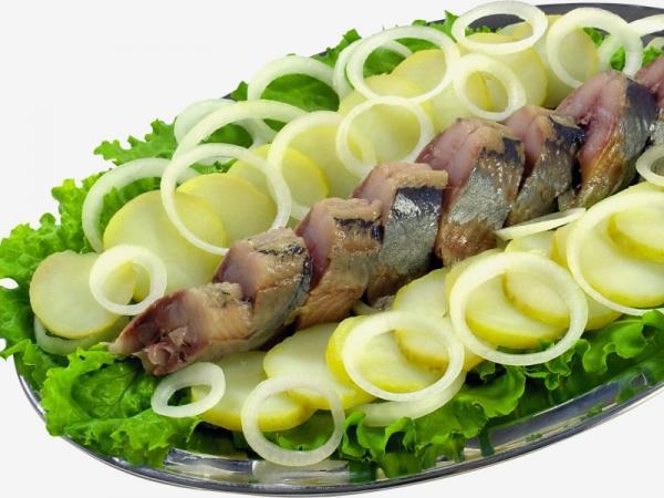 кусочки сельди на листьях салата с картошкой и луком