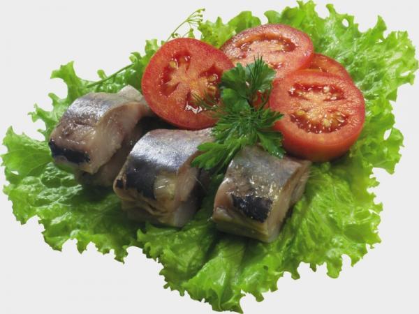 кусочки сельди на листьях салата с помидорами