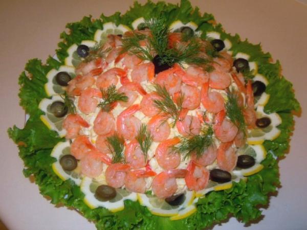 салат на блюде украшенный креветками  листьями салата и маслинами