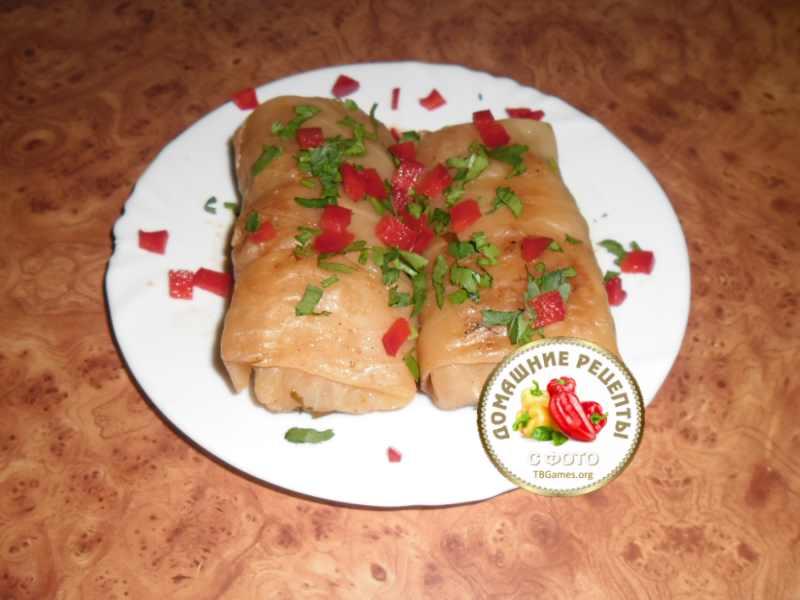 Голубцы с мясом и рисом в капустных листьях на тарелке