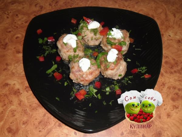 тефтели с зеленью и сметаной на тарелке