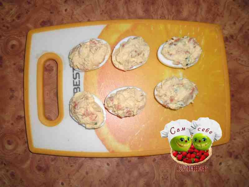 половинки яиц с начинкой на разделочной доске