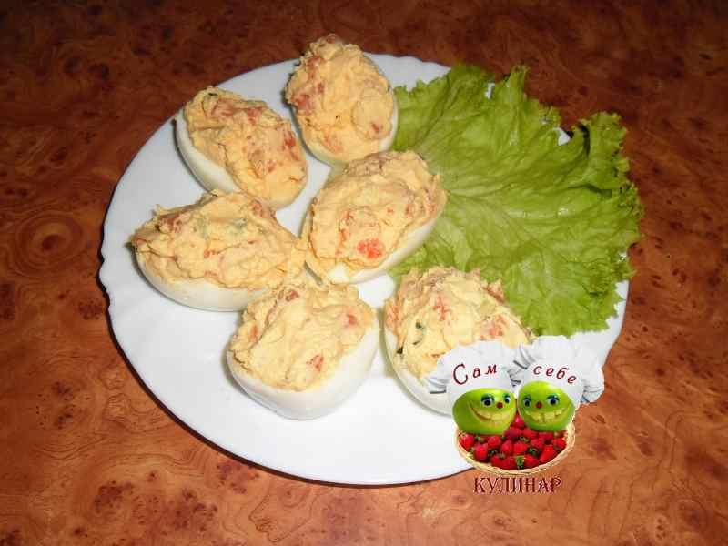 фаршированные яйца на белой тарелке лист салата